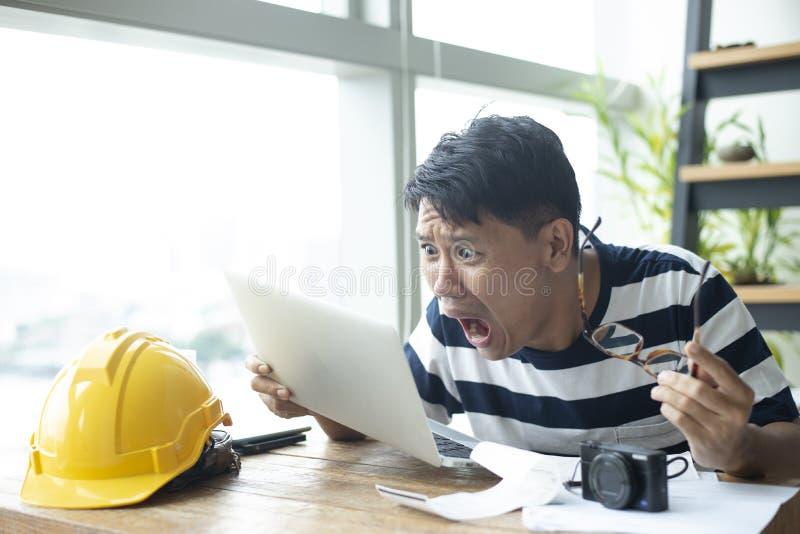 L'homme asiatique que l'ingénieur utilise le T-shirt fonctionnant libre de bande est à la maison sentiment sérieusement choquant image libre de droits