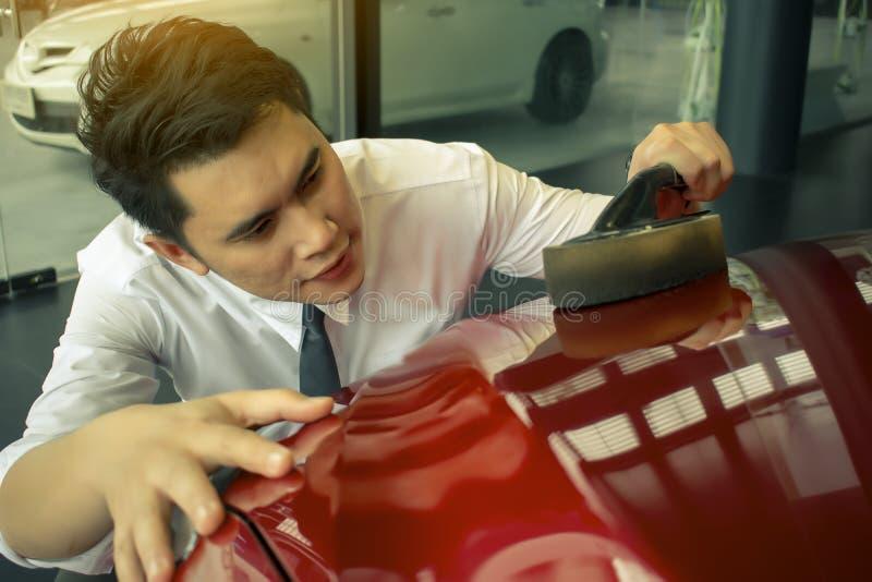 L'homme asiatique wipping la voiture avec le phare de LED pour des clients utilisation images stock