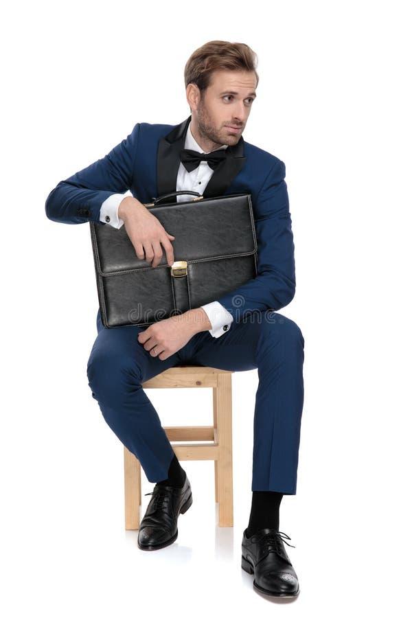 L'homme assis de mode protège une valise noire regardant loin photographie stock