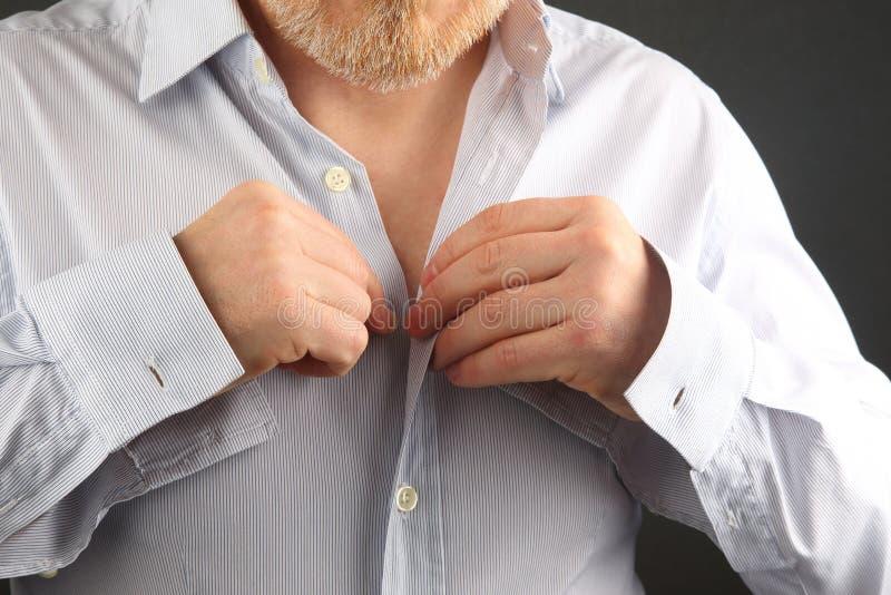L'homme attache des boutons sur sa chemise photo libre de droits