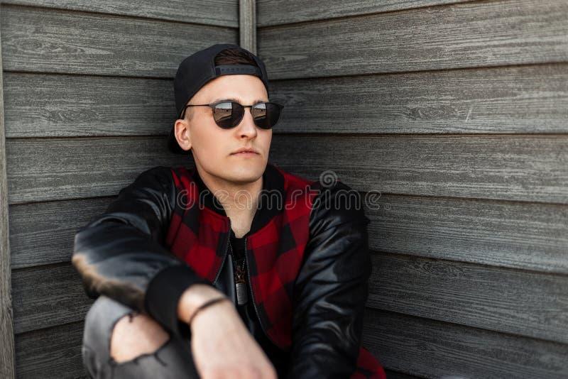 L'homme attirant à la mode de hippie dans des lunettes de soleil élégantes utilisant une casquette de baseball s'assied près d'un photos libres de droits