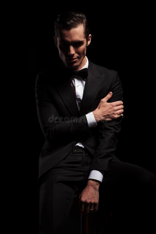 L'homme attirant dans la pose noire a posé toucher son bras image stock