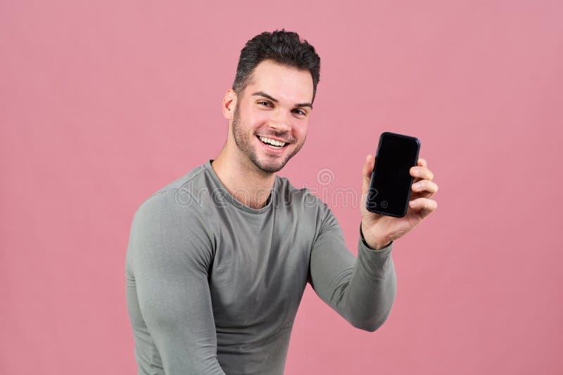 L'homme attirant sportif dans de larges sourires de T-shirt serré heureusement, tenant le smartphone disponible avec l'affichage  photos libres de droits