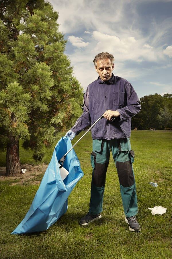 L'homme au travail prennent des déchets sur l'herbe en parc image stock