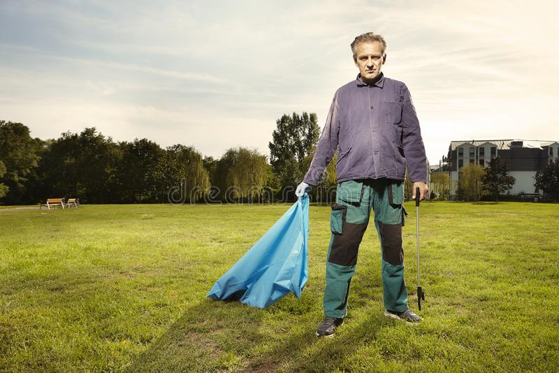 L'homme au travail prennent des déchets sur l'herbe en parc images libres de droits