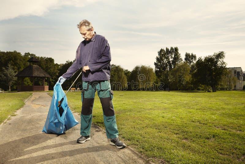 L'homme au travail prennent des déchets sur l'herbe en parc photos libres de droits