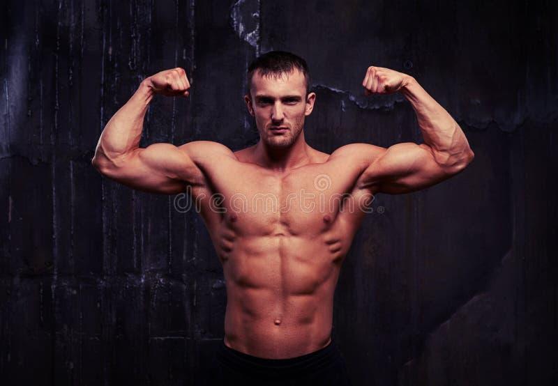 L'homme avec de l'ABS, les épaules, le biceps, le triceps et le coffre parfaits est PO photo libre de droits