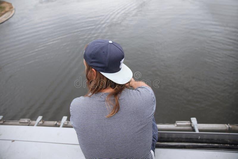 L'homme avec de longs cheveux et une casquette de baseball s'assied avec le sien de retour au bord du pont à une taille au-dessus photos stock
