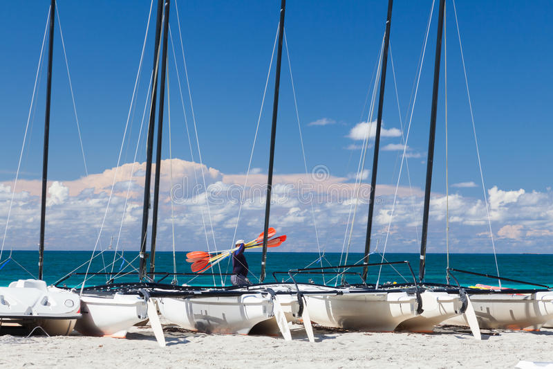 L'homme avec des avirons va sur le bord de mer Beaucoup de séjour de catamarans sur images libres de droits