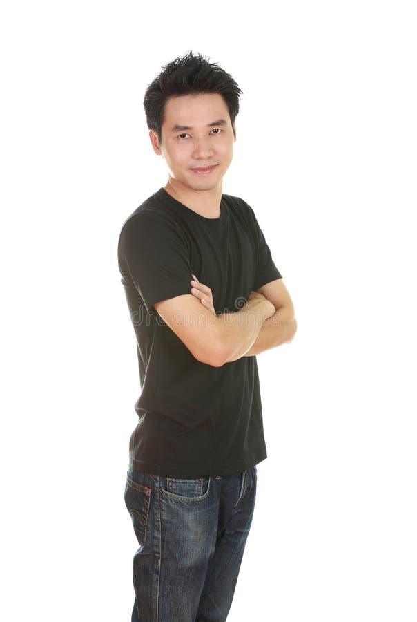 L'homme avec des bras a croisé, utilisant le T-shirt noir photographie stock
