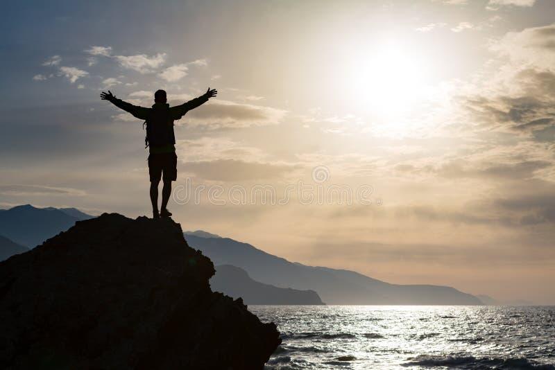 L'homme avec des bras tendus célèbrent le lever de soleil de montagnes photos stock