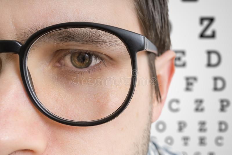 L'homme avec des verres examine sa vue Vue de plan rapproché sur l'oeil images stock