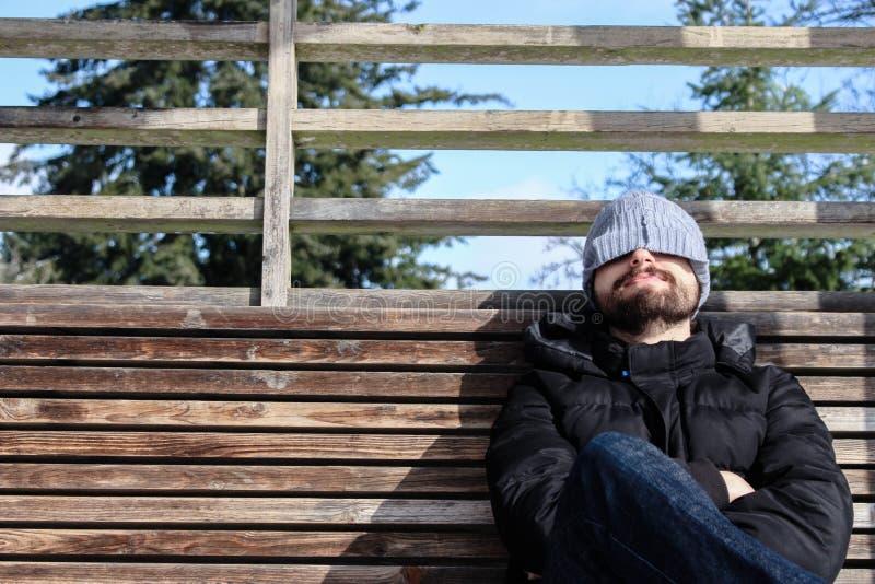 L'homme avec l'hiver vêtx, se reposant sur un banc en bois avec la neige images libres de droits