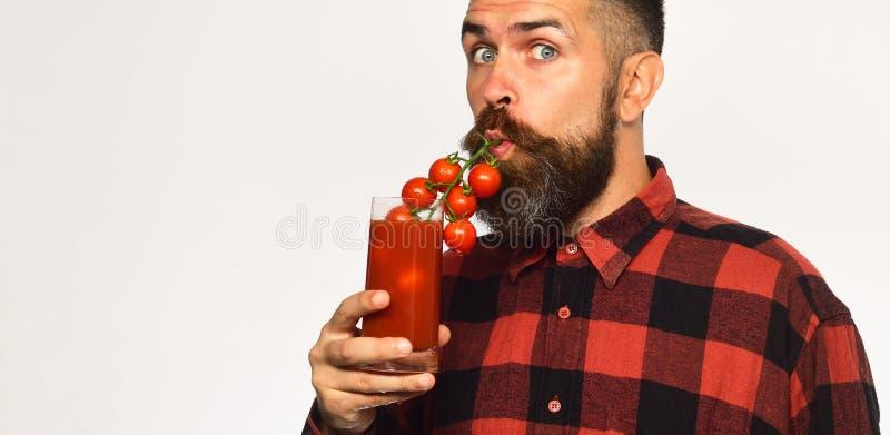 L'homme avec la barbe boit du jus de tomates d'isolement sur le fond blanc L'agriculteur avec le visage étonné emploie des tomate photographie stock libre de droits