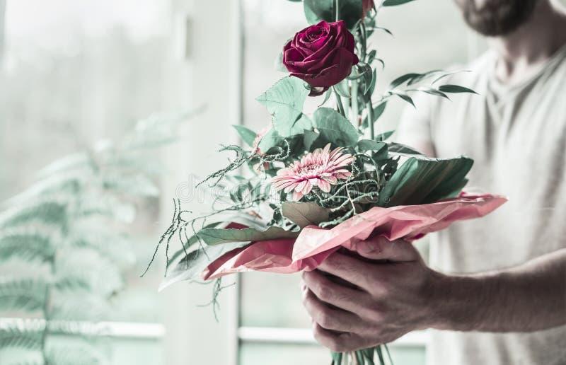 l'homme avec la barbe et dans un T-shirt gris tient un beau bouquet de fête dans les mains, dans la perspective d'une fenêtre et photo stock