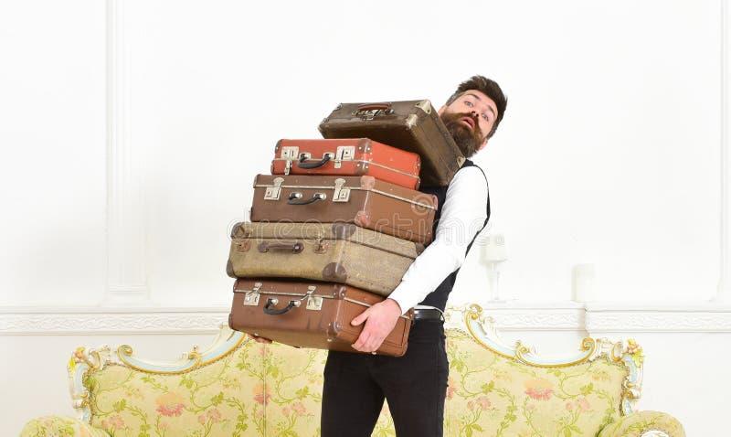 L'homme avec la barbe et la moustache portant le costume classique livre le bagage, fond intérieur blanc de luxe Butler et servic photo stock
