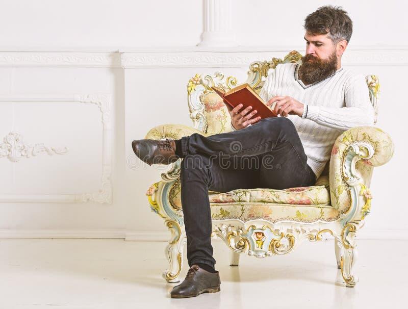 L'homme avec la barbe et la moustache s'assied sur le fauteuil et la lecture, fond blanc de mur Connaisseur de concept de littéra photographie stock