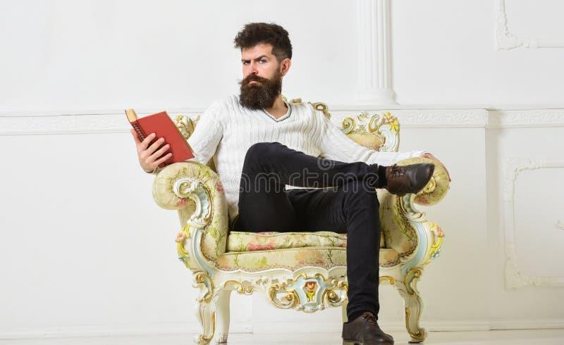 L'homme avec la barbe et la moustache s'assied sur le fauteuil et la lecture, fond blanc de mur Connaisseur de concept de littéra photo libre de droits