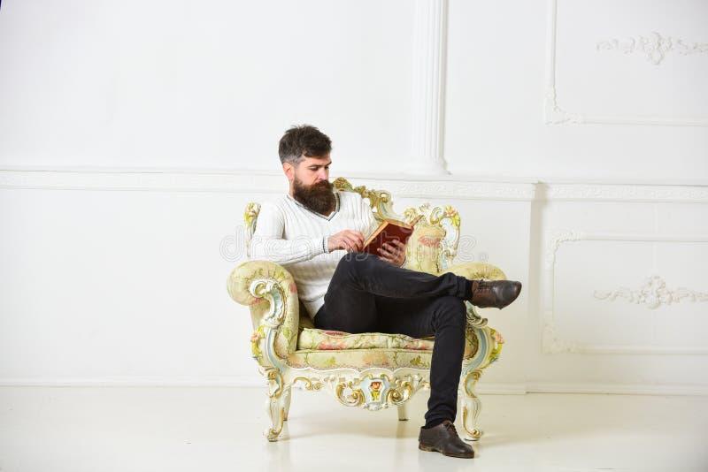L'homme avec la barbe et la moustache s'assied sur le fauteuil et la lecture, fond blanc de mur Connaisseur de concept de littéra images libres de droits