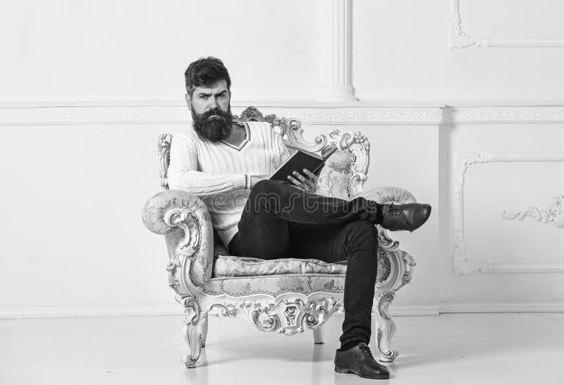 L'homme avec la barbe et la moustache s'assied sur le fauteuil et la lecture, fond blanc de mur Le connaisseur, professeur appréc photos libres de droits