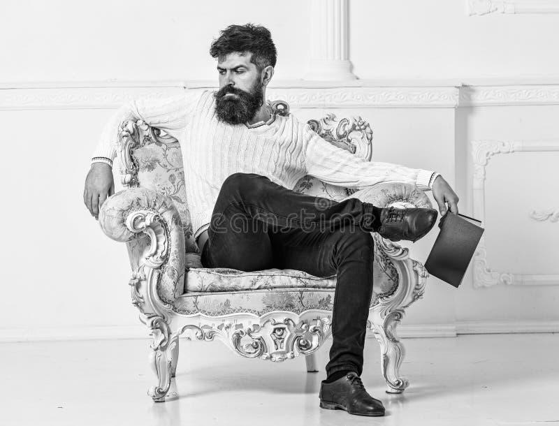 L'homme avec la barbe et la moustache s'assied sur le fauteuil, tient le livre, fond blanc de mur Connaisseur sur le visage réflé photos stock