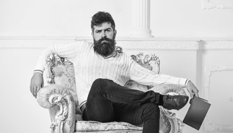 L'homme avec la barbe et la moustache s'assied sur le fauteuil, tient le livre, fond blanc de mur Connaisseur sur le visage réflé image stock