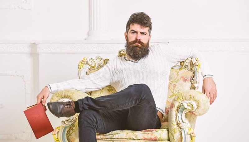 L'homme avec la barbe et la moustache s'assied sur le fauteuil, tient le livre, fond blanc de mur Connaisseur sur le visage r?fl? images libres de droits