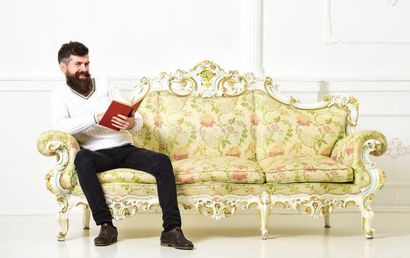 L'homme avec la barbe et la moustache s'assied sur le sofa baroque de style, tient le livre, fond blanc de mur Macho sur le visag photos libres de droits