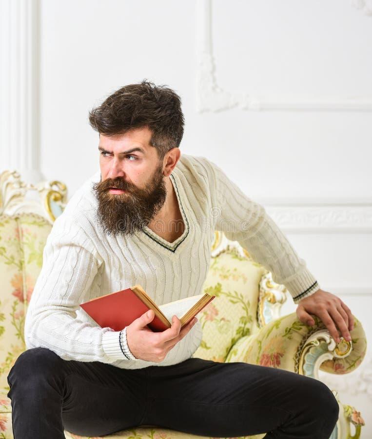 L'homme avec la barbe et la moustache s'assied sur le sofa baroque de style, tient le livre, fond blanc de mur Réflexions sur la  photo stock