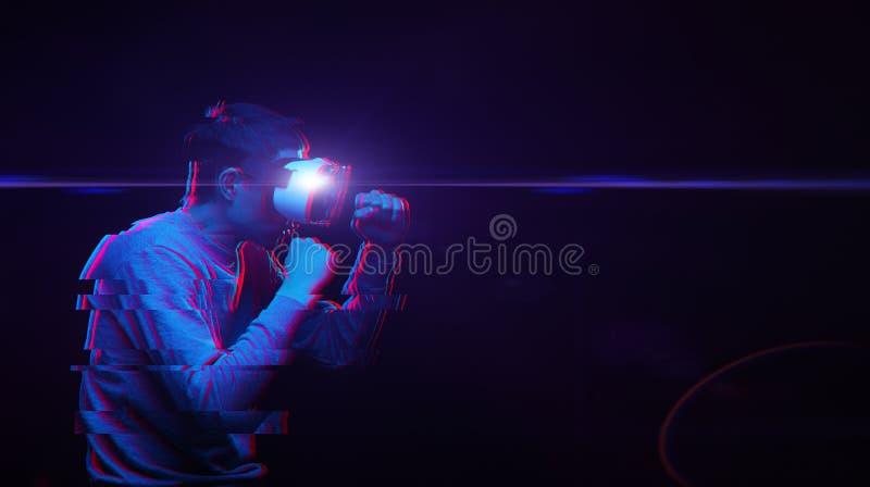 L'homme avec le casque de réalité virtuelle joue le jeu et le combat Image avec l'effet de probl?me image stock