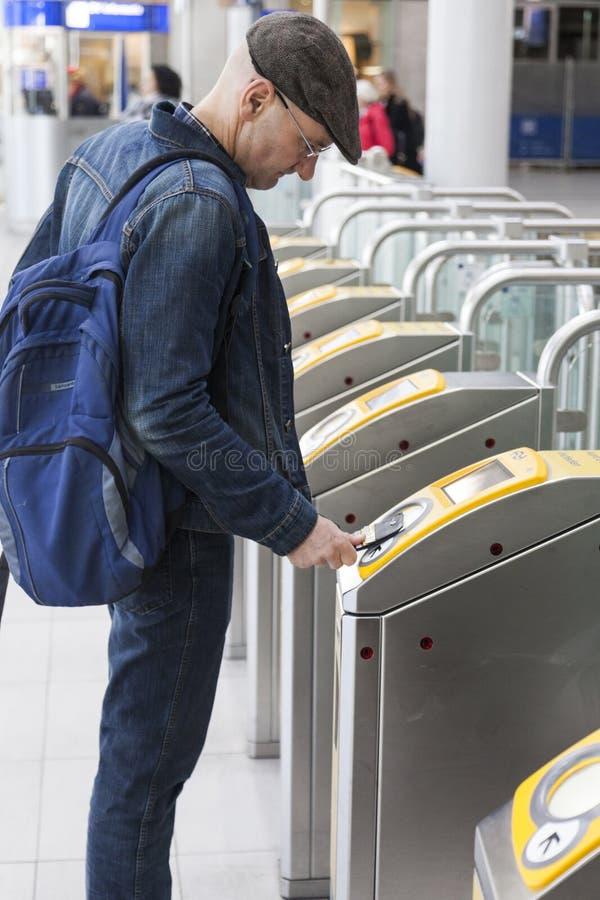 L'homme avec le chapeau signe sur la gare ferroviaire Utrecht centraal en Th photo libre de droits
