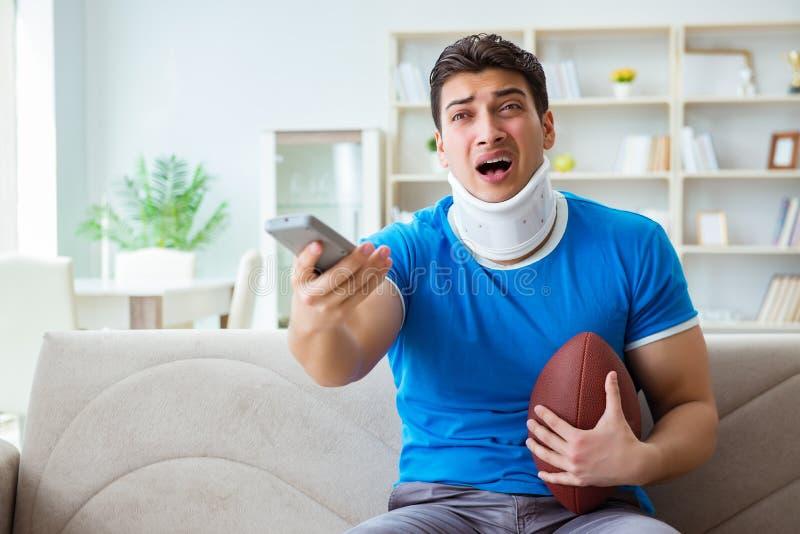 L'homme avec le football américain de observation de blessure de cou à la maison photographie stock