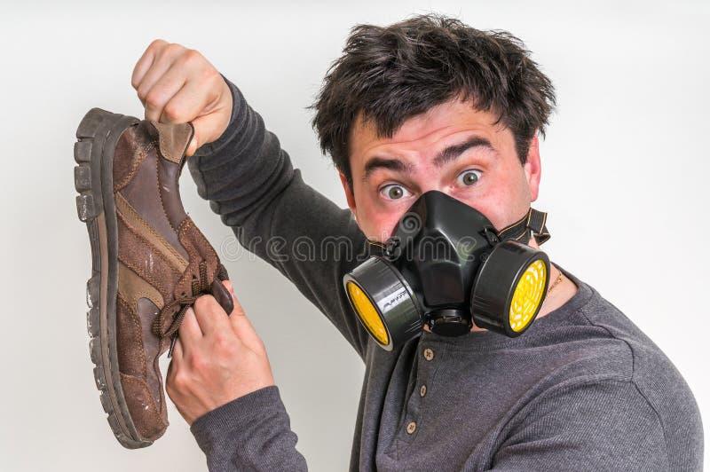 L'homme avec le masque de gaz tient la chaussure stinky images stock