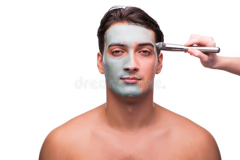L'homme avec le masque protecteur étant appliqué sur le blanc photos stock