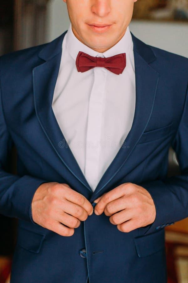 L'homme avec le noeud papillon de Bourgogne et les boutons de chemise blancs lèvent son blazer bleu-foncé images libres de droits