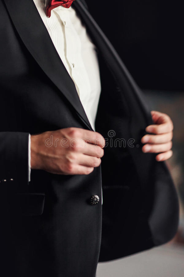 L'homme avec le noeud papillon rouge se boutonne vers le haut de son blazer noir photographie stock libre de droits