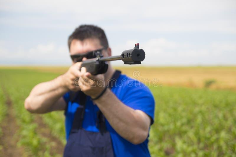 L'homme avec le pistolet pneumatique est but photographie stock