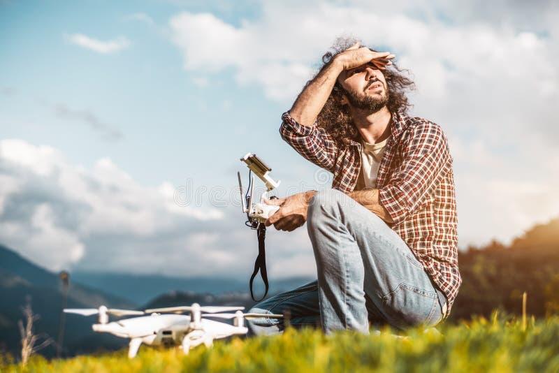 L'homme avec le quadcopter et contrôleur à distance dehors dans le mounta photos libres de droits