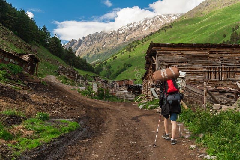L'homme avec le sac à dos entre en montagnes de Caucase photographie stock libre de droits