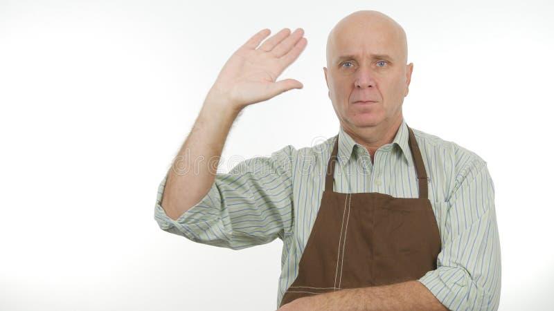 L'homme avec le tablier font bonjour à signe des gestes de main de salut photographie stock libre de droits