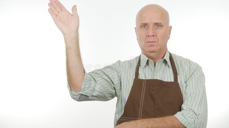 L'homme avec le tablier font bonjour à signe des gestes de main de salut images libres de droits