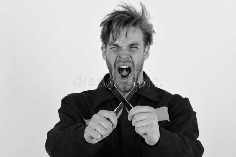 L'homme avec le visage fou juge des outils de clé croisés sur le fond blanc Entretien et concept de réparation Mécanicien ou plom images stock