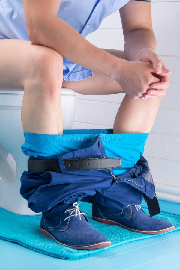 l'homme avec ses sous-vêtements vers le bas et chaussures bleues s'assied sur la toilette images libres de droits