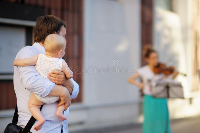 L'homme avec son fils écoutent violoneur photos libres de droits