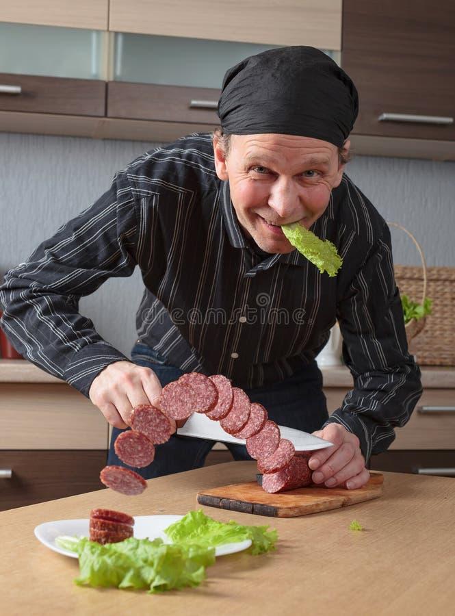 L'homme avec un couteau coupe la saucisse de morceaux photographie stock libre de droits
