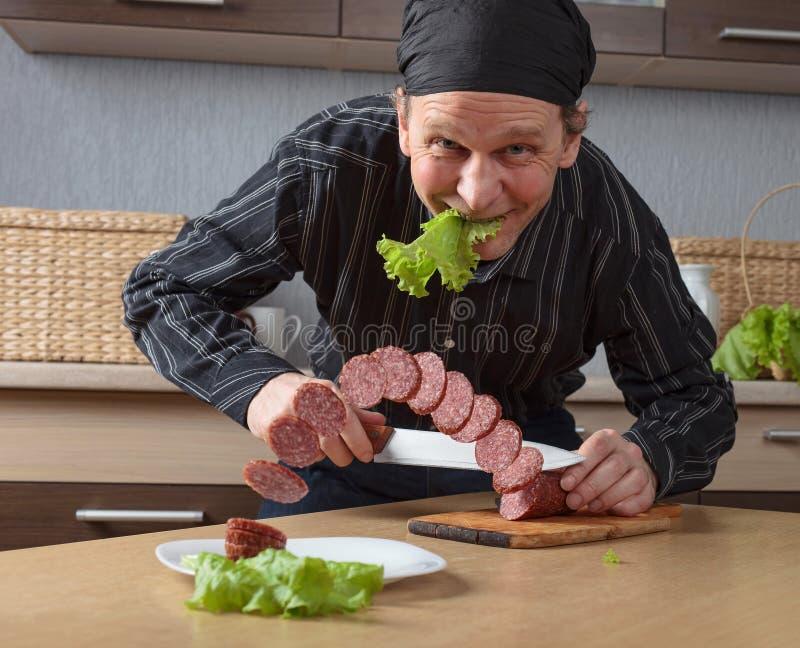 L'homme avec un couteau coupe la saucisse de morceaux photo libre de droits