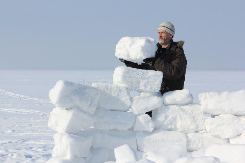 L'homme avec une barbe dans un chapeau gris construisant un igloo images stock