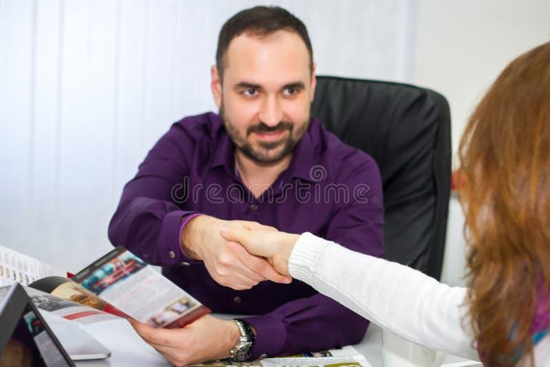 L'homme avec une barbe lors d'une réunion serre la main à une fille images stock