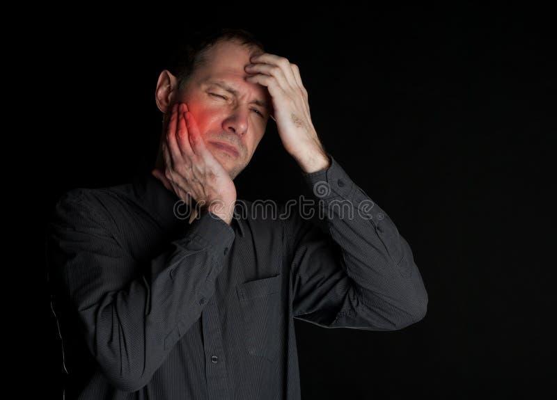L'homme avec une dent malade garde la main de joue Sur un fond noir image libre de droits