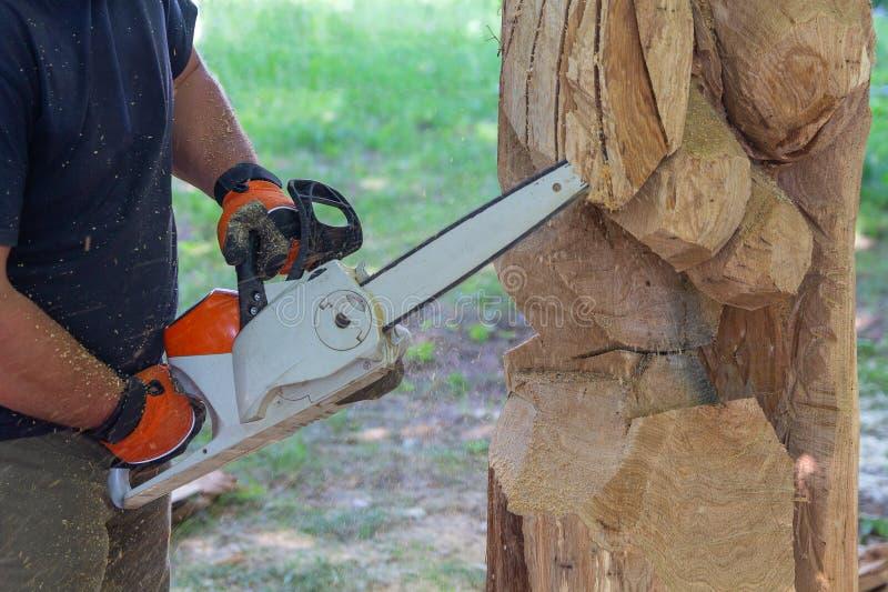 L'homme avec une tronçonneuse crée une sculpture faite de bois images stock
